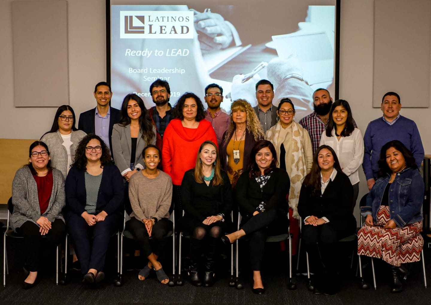 Young women and men smiling, in professional attire, grouped together for a photograph after a Latinos LEAD event